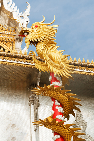 Golden dargon statue in front of Buddhist temple. Stock Photo