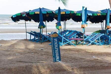 Chonburi, Thailand - June 12, 2018: Bangsaen beach with beach chair and umbrella. Word on post is Bangsaen beach.