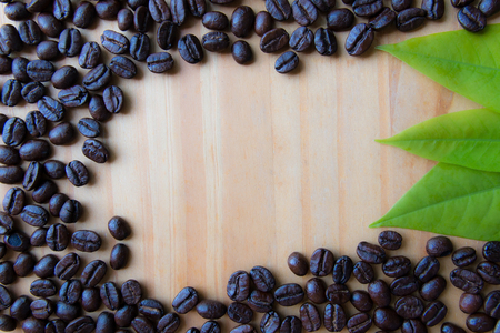 Roasted coffee beans and leaves with copy space background.