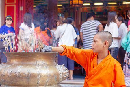 Nonthaburi, Thailand - January 1, 2013: Young monk keep incense at Wat Mangkon Kamalawat, Chinese temple.
