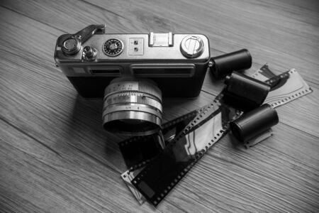Rangefinder use film camera on wood table with black and white style.