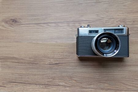 Bangkok, Thailand - September 8, 2019: Rangefinder use film camera on wood table with copy space.