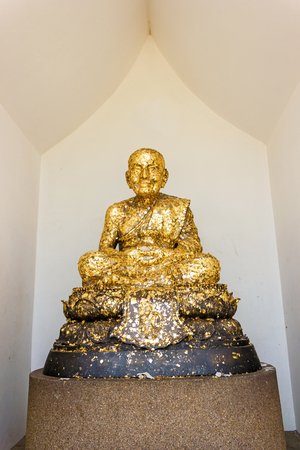 Golden monk Buddha statue in temple.
