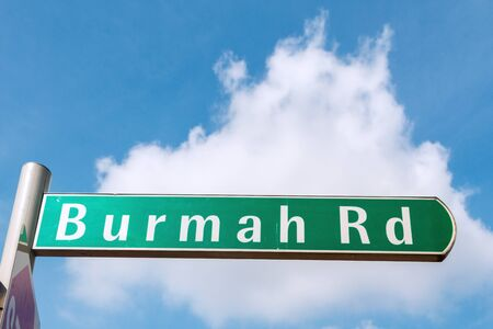 Road sign in Singapore. Word is Burma road with blue sky background.
