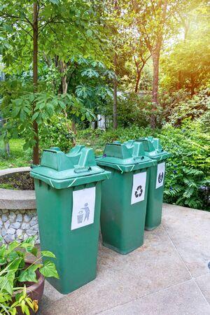 Three green bins in garden.