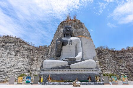 Stone Buddha statue at Wat Khao Tham Thiam, Suphanburi, Thailand.