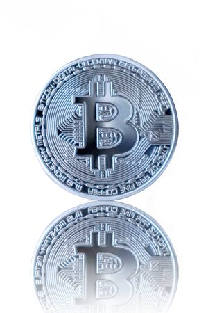 Silver Bitcoin reflection on white isolated background.