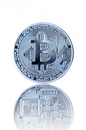 Silver Bitcoin reflection back on white isolated background.