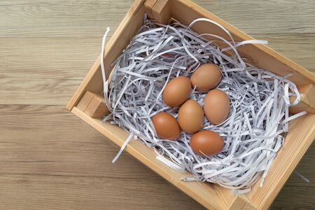 Eggs straw paper in wooden box with copy space.
