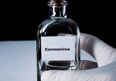Dark background and close-up of white glove right hand holding a bottle with a cork lead and a label spelling Coronavirus.