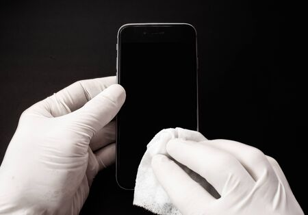 Left hand is holding the smartphone and the right hand is cleaning it with a white wipe with black background.