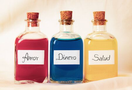 Three glass bottles red blue and yellow with the words Amor Dinero Salud written in Spanish. The bottles use a cork lead and the background is a white sheet with a strong light.