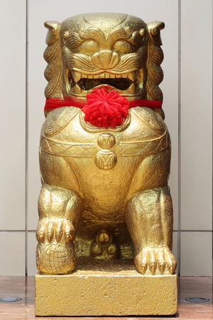 Chinese Golden lion statue with red ribbon
