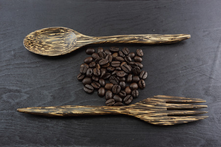 Coffee crop beans with Wooden Spoon and wooden background photo