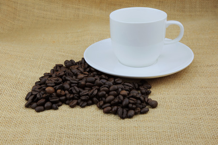 addictive drinking: coffee beans and coffee cup on the hemp sack