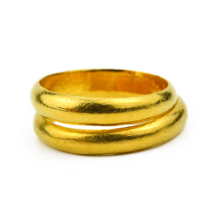 gold jewellery: close up of Two gold rings on white background