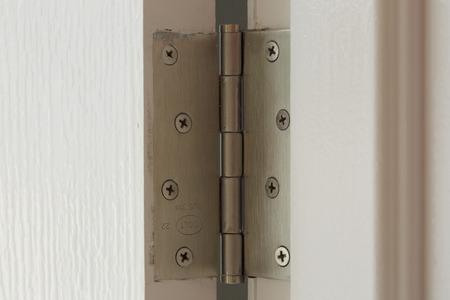 steel door: stainless door hinges on a white door Stock Photo