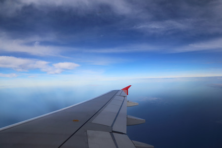 private airplane: Wing of airplane flying above the clouds in the sky Stock Photo