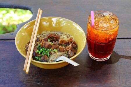 toon: Noodles with pork with soup Thai style and ice tea. Thai peoples call braised pork Noodles or Moo toon