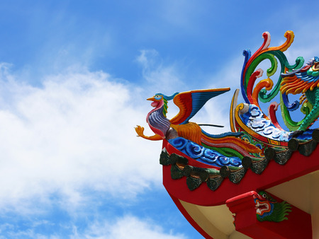 chinese phoenix: Phoenix statue on the roof of a Chinese temple under cloud and sky