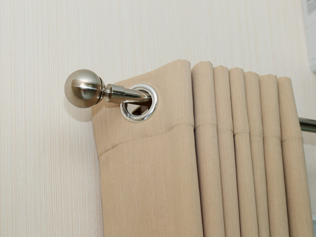 cream colored: Cream colored curtains In steel rail close up view