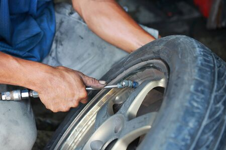 working tools: close up of Detail image of mechanic hands with tool, changing tyre of car