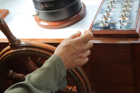 old ship: close up of mans Hands hold steering wheel the boat on daytime Stock Photo