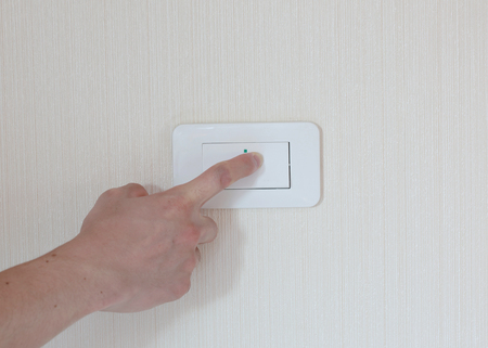 turn about: man hand with finger on light switch, about to turn on the lights. Stock Photo
