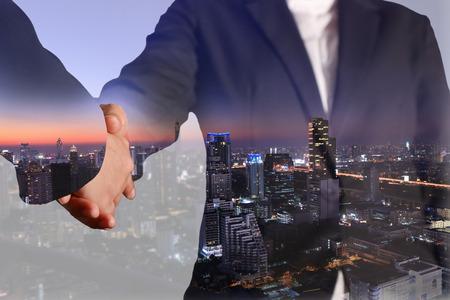 compromiso: Doble exposición de apretón de manos y la ciudad de noche, tono azul Foto de archivo