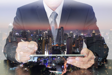 Double exposure of businessman working with tablet and night city Banco de Imagens