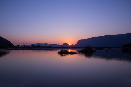 gloaming: view of sunset and mountain water reflection in gloaming time