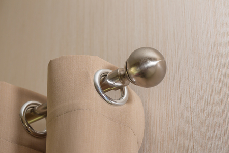 cream colored: close up of steel knob and Cream colored curtains