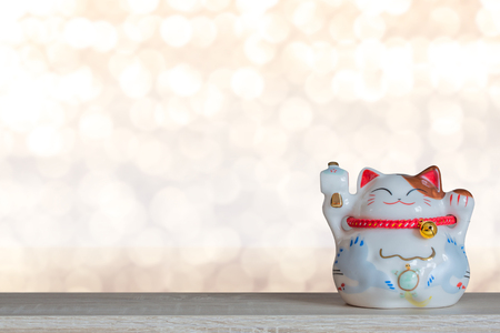 beckoning: Beckoning lucky cat piggy bank with light bokeh background, abstract background to time to start to saving or lucky for keep money concept.