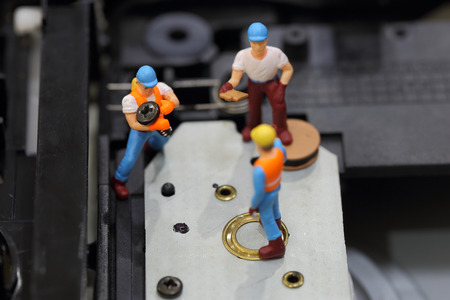 cd rom: Selective focus of miniature engineer and worker fixed to hold screw for repair cd rom of computer and use for business background.