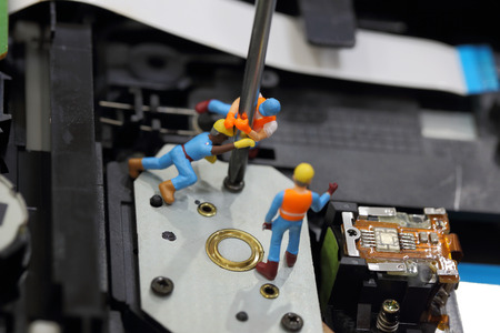 cd rom: Selective focus of miniature engineer and worker fixed to remove screw by screwdriver for repair cd rom of computer and use for business background.