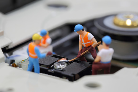 cd rom: Selective focus of miniature engineer and worker fixed to clean CD rom reader of mainboard computer and use for business background.