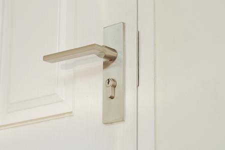 白い扉の横に金属のノブ