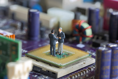 Selective focus of miniature businessman handshake on Control Processing Unit (CPU),  mainboard computer as Partners and Industry concept. Stock Photo
