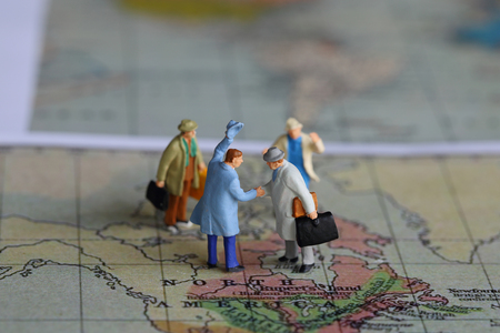 figurine: Selective focus of miniature businessman handshake on North America map background as Journey and travel Concept