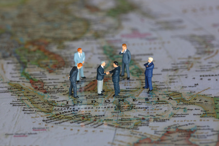 Selective focus of miniature businessman handshake on Indonesia map background as commitment, agreement and travel Concept