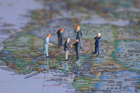 Selective focus of miniature businessman handshake on Nigeria world map background for Trade and Investment background as commitment, agreement and partnership Concept Stock Photo