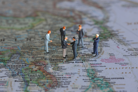 altogether: Selective focus of miniature businessman handshake on Hong Kong, Shenzhen or Taiwan world map background as commitment, agreement and partnership Concept