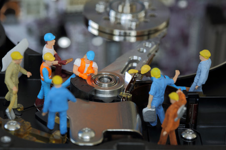 Selective focus of miniature engineer and worker maintenance hard disk or fixed problem hard disk of Personal computer (PC) as business and industrial concept. Stock Photo
