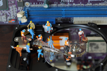 fixed disk: Selective focus of miniature engineer and worker maintenance hard disk and fixed problem hard disk of Personal computer (PC) on blurred mainboard background as industrial concept.