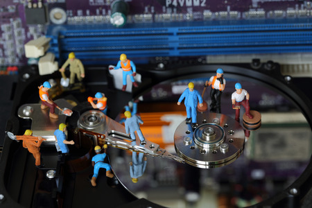 fixed disk: Selective focus of miniature engineer and worker maintenance hard disk and fixed problem hard disk of Personal computer (PC) on blurred mainboard background as business and industrial concept.