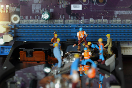 fixed disk: Selective focus of miniature engineer and worker repair hard disk and fixed problem hard disk of Personal computer (PC) on blurred mainboard background as business and industrial concept.
