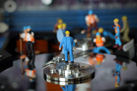 headman: Selective focus of miniature engineer Headman control to fixed problem hard disk of Personal computer (PC) on blurred mainboard background as business and industrial concept.