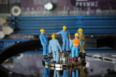 headman: Selective focus of miniature engineer Headman meeting to fixed problem hard disk of Personal computer (PC) on blurred mainboard background as business and industrial concept.