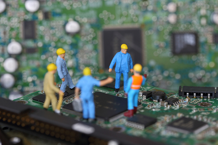 mainboard: Selective focus of miniature engineer and worker meeting to fixed problem chipset of Personal computer (PC) on blurred mainboard background as business and industrial concept. Stock Photo
