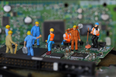 Selective focus of miniature engineer and worker fixed problem on chips and computer mainboard as business and industrial concept. Standard-Bild